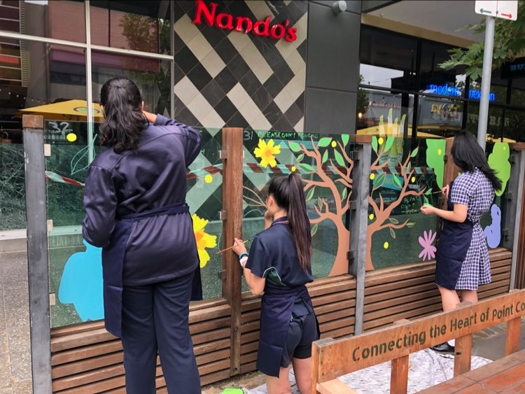 Primary school children painting on the glass partitions of restaurants and businesses on Murnong St.
