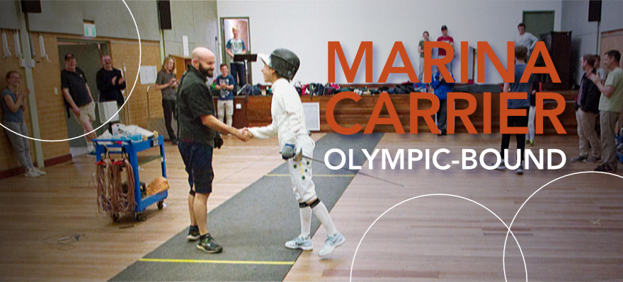 Marina Carrier and coach Jo Raciborski shake hands on the piste after a bout at the MFC training venue. Some members and spectators stand at the sides applauding and smiling. This bout was pretty dynamic! I think we all know who won that one. Sorry Joe, you may have amazing calves but Marina is small and mighty! Forza Marina!