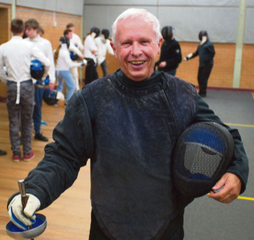 Richard Emmerick resplendent in coaching blacks holding his mask under his left arm and his epee in his right hand with its point to the ground, he faces the camera smiling in the fencing hall, in the background a line of young fencers work with two of the coaches. He looks happy and why shouldn't he be? He founded the club and it's the best!