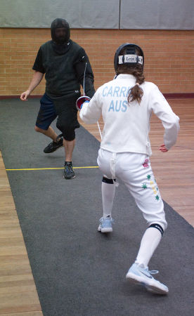 Marina Carrier and Joe Raciborski stand en guard ready to spring. The shot is taken from behind Marina as she faces Joe on the piste. The back of her jacket shows the stencil 'CARRIER AUS' and we can see the southern cross on the right leg of her breeches. Both are lefties, cancelling out the left handed advantage!