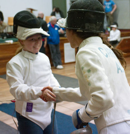 Marina Carrier shakes the hand of the young fencer she has just bouted with. Both have their masks pushed back on the tops of their heads, it IS a thing! The young fencer smiles and, although we can't see Marina's face because the shot is taken from behind her and to the side, I reckon she is smiling too. She's actually such a beacon of positivity that she always seems to be smiling! Yeah, we're fans.